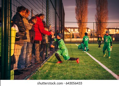 VINOR, PRAGUE, CZECH REPUBLIC -  NOV 20, 2016: Happy school boy soccer player celebrates victory, shaking hand with his father standing with other parents - fans behind football field fence