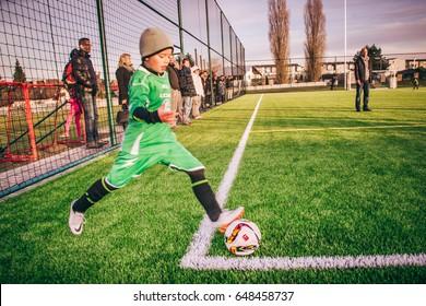 VINOR, PRAGUE, CZECH REPUBLIC -  NOV 20, 2016: Forward player of Loko Vltavin kicks off corner kick at after school football match in Vinor. Picking up parents watch and cheer for their children