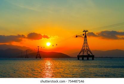 VINPEARL RESORT, NHA TRANG, VIETNAM - FEBRUARY 01, 2015: Cable car Colorful Sky At Sunset Dawn Sunrise, cableway long rope road on water bay Nha Trang, Vietnam