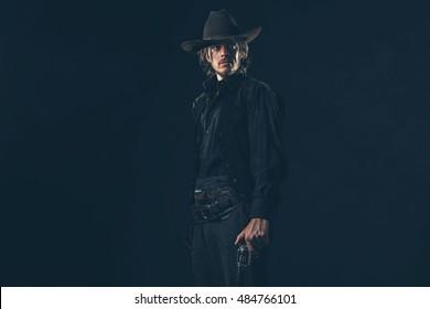 Vintage 1900 cowboy. Young man. Studio shot against dark wall.