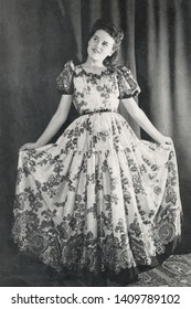 Vintage 1940s portrait of a smiling young woman wearing a silk wide-ranging flower dress.