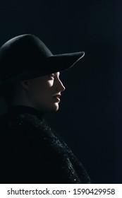 Vintage 1940s woman in black hat. Side view.