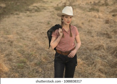 Vintage 1950s cowgirl in red checkered shirt and blue jeans in field.