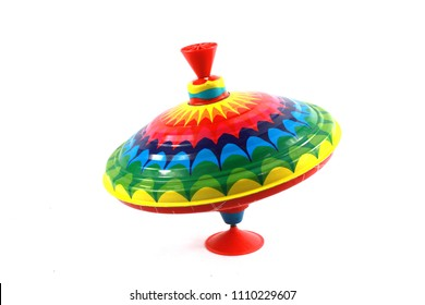 A Vintage 1970s Children's Spinning Top in Rainbow Colours on White Background