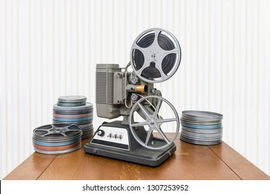 Vintage 8mm home movie projector and film cans on wood table.
