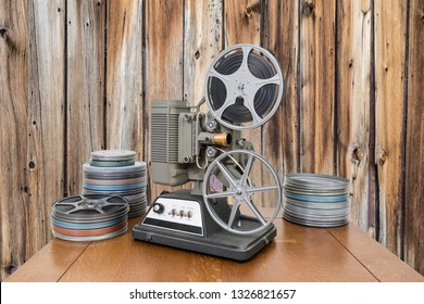 Vintage 8mm home movie projector and film cans with old wood wall.
