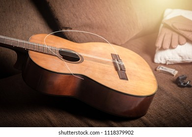 vintage acoustic guitar with breaked string on the sofa.