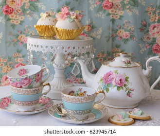 Vintage afternoon tea party - blue floral tea cup and saucer, pink roses teapot and white cake stand with cupcakes on a floral table cloth
