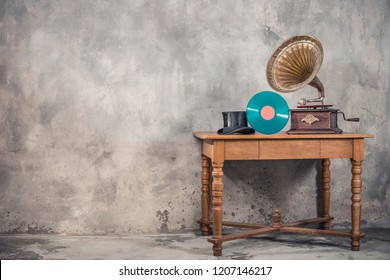 Vintage aged brass gramophone phonograph turntable, turquoise vinyl disc and antique gentleman's cylinder hat on wooden table front concrete wall background. Retro old style filtered photo