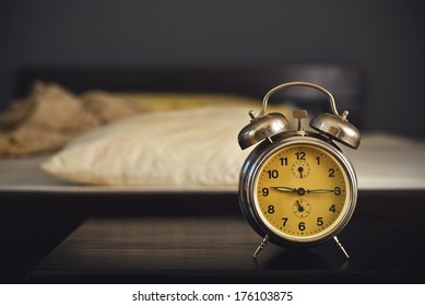 Vintage alarm clock in bedroom on a night table by the bed.