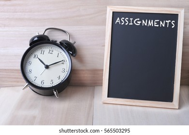 Vintage alarm clock and a blackboard with word ASSIGNMENTS on it with wooden background. Time management, business and financial concept.