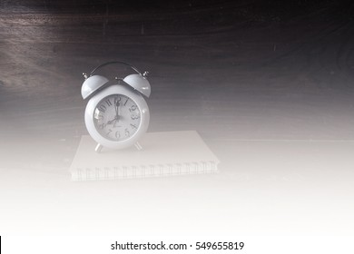 Vintage alarm clock with eight  o'clock. Old style photo. Black and white tone.Book.
