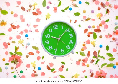 Vintage alarm clock flat lay with colorful springtime floral decoration of petals and leaves