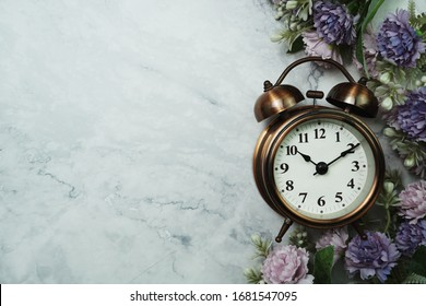 Vintage Alarm Clock And Flower Bouquet with space copy on marble background