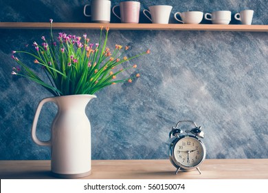 Vintage alarm clock with flower in jug on table and various cups background