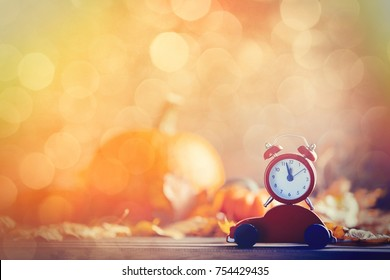 Vintage alarm clock and maple tree leaves with little cart toy on yellow wooden background with bokeh. Autumn season image style for Thaksgiving holiday