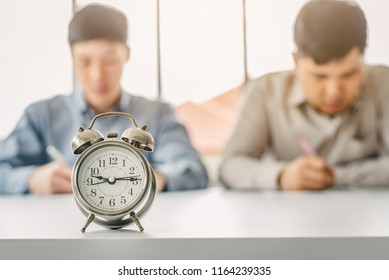 Vintage alarm clock with men doing test or paper work in background