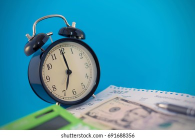 Vintage alarm clock and money - accounting concept, blurred background different focus