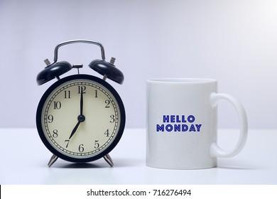 Vintage alarm clock with a mug written HAPPY MONDAY