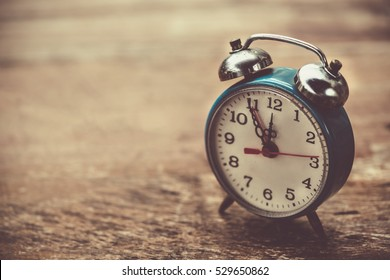 Vintage alarm clock nearly midnight time on weathered wood background, new year concept.