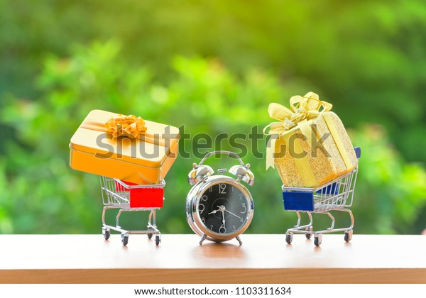 Vintage alarm clock old retro style with  modern golden gift box on chopping cart over green burred background. education or holiday concept. copy space for add text or advisement.