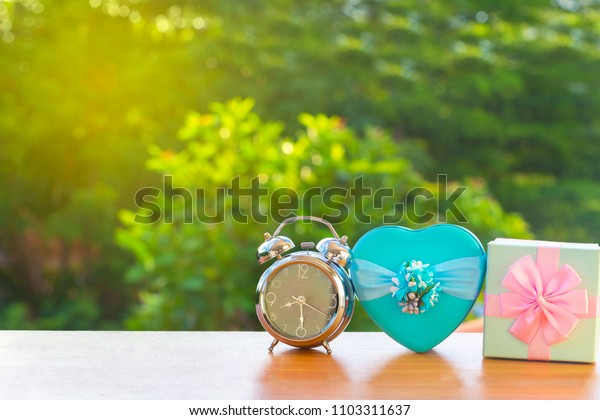 Vintage alarm clock old retro style with modern gift box on green burred background. education or holiday concept. copy space for add text or advisement.