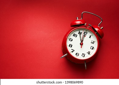 Vintage Alarm Clock On Red Background. Alarm clock showing five to midnight.