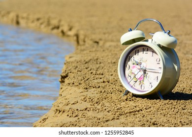 A vintage alarm clock on a sandy beach with small stream of sea water flowing to the ocean.