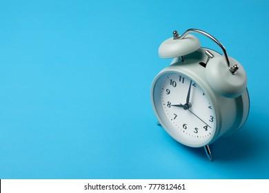 vintage alarm clock on solid light blue color background