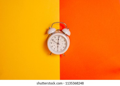 Vintage alarm clock on two tone solid color yellow and orange background. Early morning