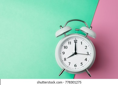 vintage alarm clock on two tone solid color green and pink background