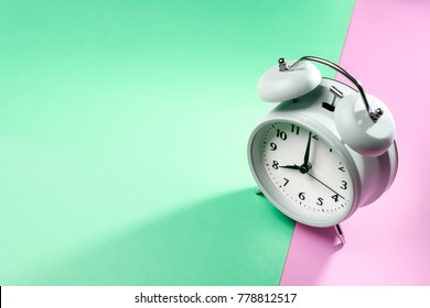 vintage alarm clock on two tone solid color green and pink background with hard light and long shadow