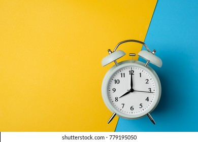 vintage alarm clock on two tone solid color yellow and light blue background