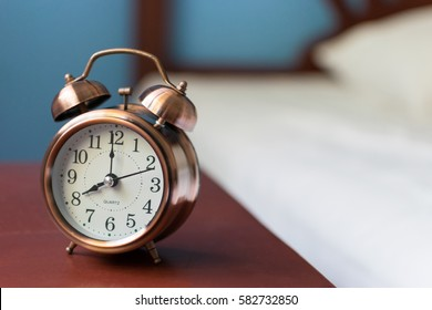 vintage alarm clock on wood table at 8 o'clock.