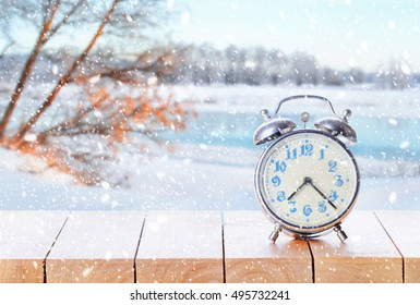 Vintage alarm clock on wooden table or bench in snowy weather on winter background. Return to winter time. Fall back time. Daylight savings end. Switched to winter time changing clock from wintertime.