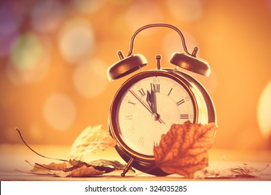 Vintage alarm clock on yellow background with bokeh