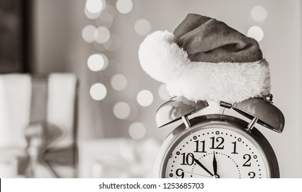 Vintage Alarm clock in Santa Claus hat with Christmas gift and Ligths on background