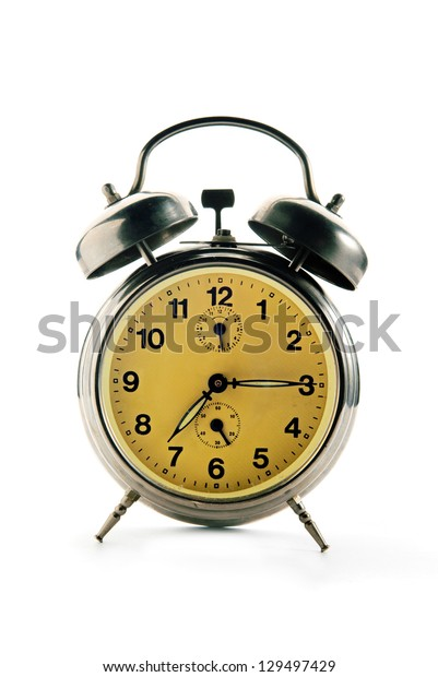 Vintage alarm clock showing quarter past seven over a white background.
