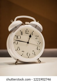 Vintage Alarm Clock standing on a white desk with brown blurry sofa in background