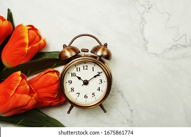 Vintage Alarm Clock And Tulip Bouquet with space copy on marble background