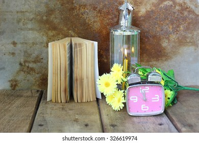 Vintage alarm clock, yellow flower, old book and lamplight on wooden table. Still Life