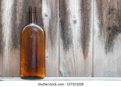 Vintage amber pharmaceutical bottle against a weathered and stained wooden background.