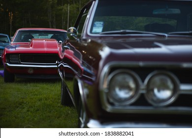 The vintage American car is in the front and out of focus, and another classic car of 1967 or 1969 is in the focus in the background.