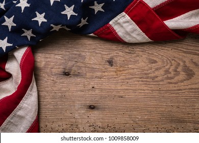 Vintage American flag bordering a worn out weathered wooden plank with space for text