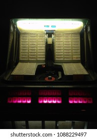 Vintage American jukebox lite up, in a dark room