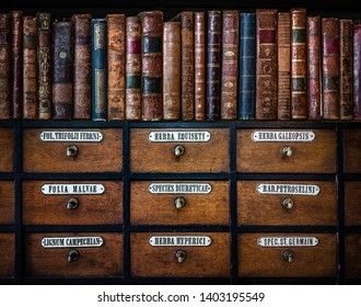 Vintage, antiquarian books on wooden old pharmaceutical cabinet. Translation from Latin language names of medicines funds: horsetail, hemp, mallow leaves, diuretic, parsley, St. John's wort, trefoil.