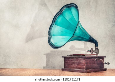 Vintage antique aged aquamarine gramophone phonograph turntable on wooden table front concrete wall background with its shadow. Retro old style filtered photo