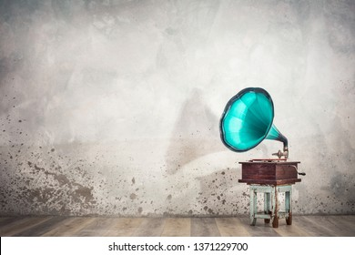 Vintage antique aged aquamarine gramophone phonograph turntable on aged wooden stool front concrete wall background with its shadow. Retro old style filtered photo