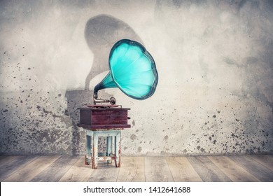Vintage antique aquamarine gramophone phonograph turntable on aged wooden blue stool front grunge textured loft concrete wall background with dramatic horn shadow. Retro old style filtered photo