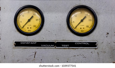 Vintage antique automotive machine shop vacuum gauges on a silver sheet metal plate with sign